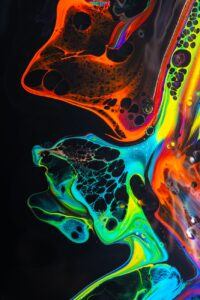 colorful mix of neon paints swirling on black surface